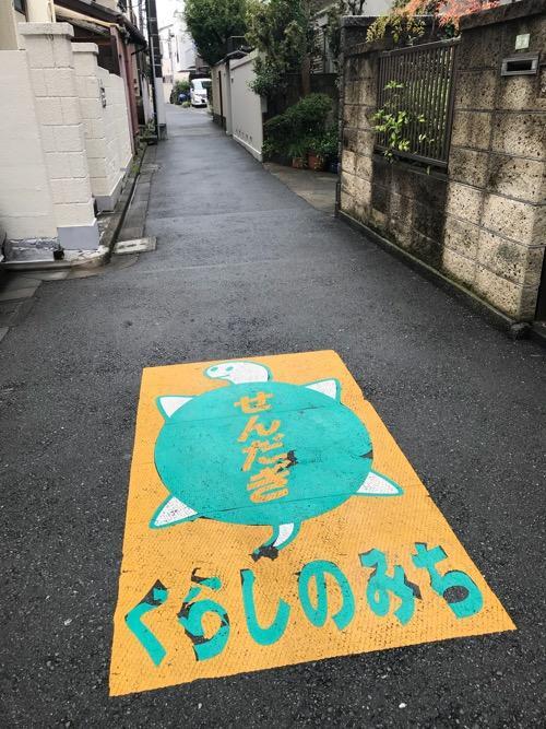 東京都文京区千駄木の「せんだぎ くらしのみち」の亀のイラストが描かれた狭い道路