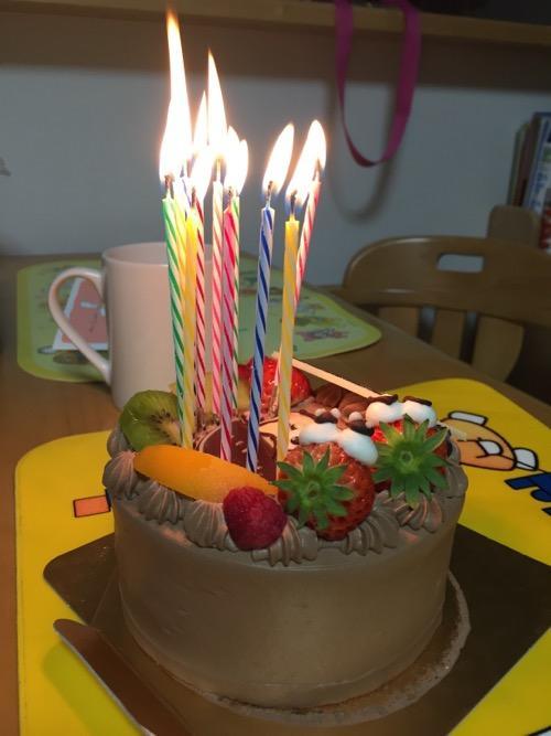 火がついた11本のろうそくとおそ松さんの誕生日ケーキ