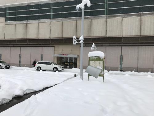 金沢駅西口の雪景色と「駅西広場」の看板(新しい地図が雪の重みで剥がれて古い地図が見えている様子)