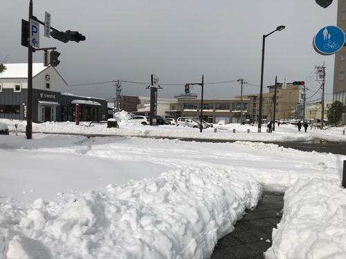 石川県庁駐車場前交差点と雪景色(左奥の建物は星乃珈琲店 石川県庁前店)