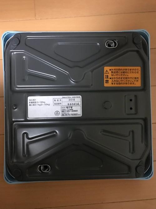 床の上に置いたタニタ 体重計 アナログヘルスメーター HA-851-BL ブルーの裏側