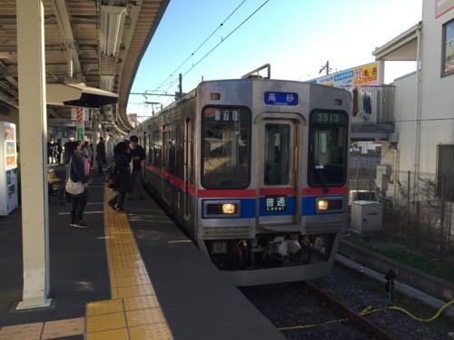 京成金町駅のホームに停車中の高砂行きの電車への乗車を待つ人々