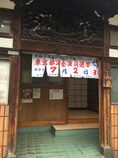 東京都足立区の銭湯・タカラ湯の玄関と東京都議会議員選挙のノレン