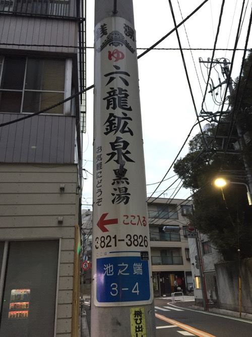 電柱に貼られている銭湯・六龍鉱泉への案内標識(看板)