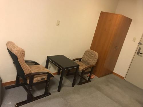 飛騨古川スペランツァホテルの肘掛け椅子とテーブル、タンス