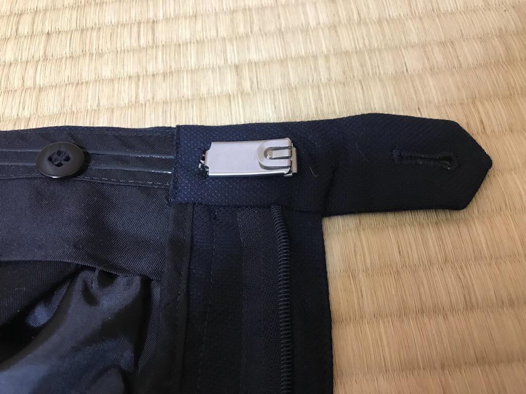 スーツのズボンのホックに「ジャストフィットかん」を装着した様子