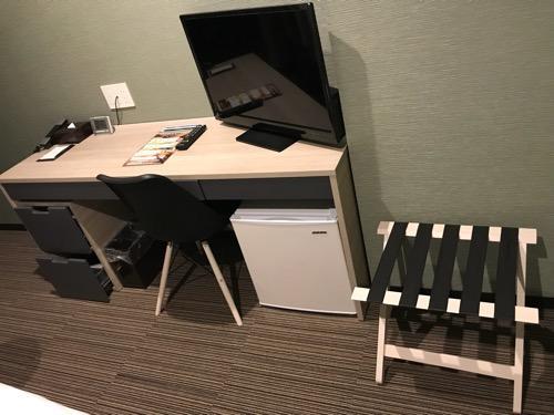 くれたけイン名古屋久屋大通のシングルルームの長机、テレビ、椅子、荷物置き台
