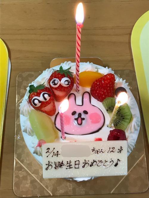 火のついた太いローソク1本、細いローソク2本が立つカナヘイさんのピンクのうさぎの誕生日ケーキ