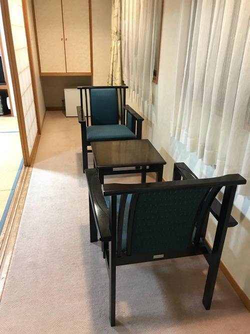 飛騨古川スペランツァホテルの窓際のテーブルと机と奥の冷蔵庫