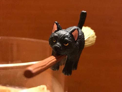 カフェベローチェ綾瀬店のアイスカフェオーレのコップのフチにホウキでまたがる猫(正面・拡大)