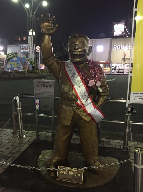JR亀有駅(北口)にある、「40年間お疲れ様」のタスキをかけられたこち亀の両さん像