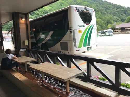 平湯バスターミナルの足湯と4番バス乗り場に停車中の濃飛バスの飛騨古川発・新宿行の高速バス