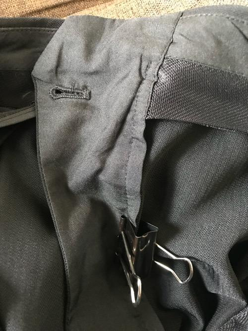 ズボンの壊れたチャックを裏側からダブルクリップで止めて応急処置をしている様子