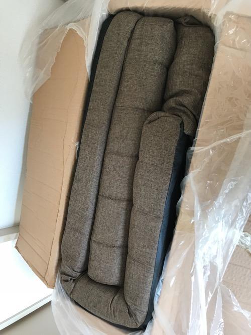 リクライニングソファ BONOの段ボール箱の中でソファーが折りたたまれている様子(梱包用のビニール袋を外した直後の様子)