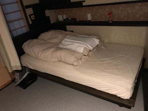 湯之谷温泉のゲストハウス部屋「海」の部屋内のベッド(シーツ等の装着前)