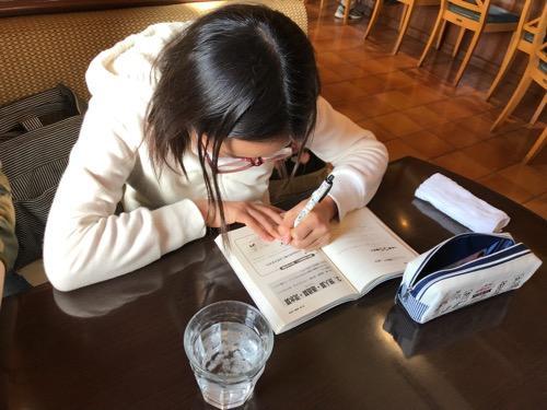 三日月とカフェ新空港通り店で算数の勉強をする小学六年生の娘