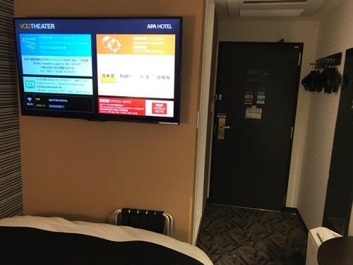 アパホテル福島駅前のシングルルームのベッド、壁掛けの大型液晶テレビ、入口ドア