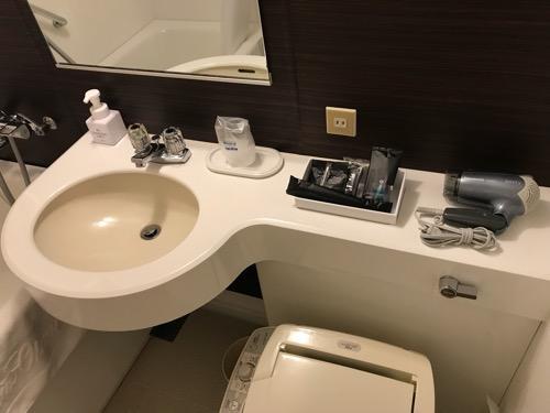 ホテルニューオータニ高岡の客室入口から見た禁煙シングルルームのユニットバス内の洗面台、ドライヤー