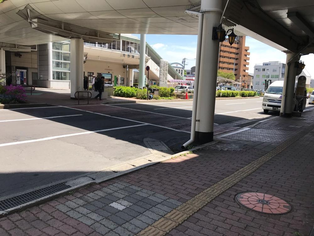 長野県茅野市のマンホールの蓋(タイルの装飾付)とJR茅野駅の駅舎