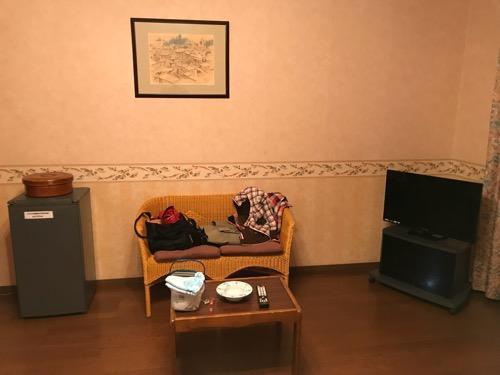 星乃岡温泉 千湯館 家族風呂・宿泊用の部屋「石の湯 305号室」の冷蔵庫、椅子、テーブル、テレビ