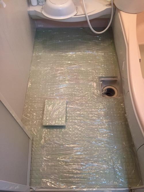 自宅の浴室の黒ずんだ床の上にティッシュを敷いて、その上にサンポールの液体を散布し、液体が乾燥しないようにラップで覆っている様子