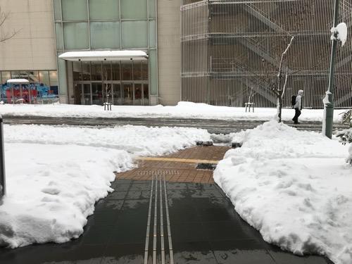 ドーミーイン金沢の出入口前の雪景色(正面の建物は金沢フォーラス)