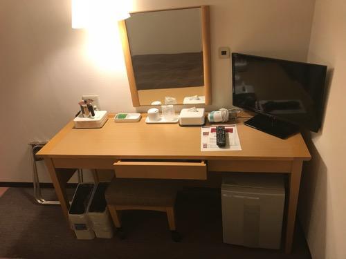 グレイスイン名古屋シングル禁煙ルームの机、椅子、鏡、テレビ