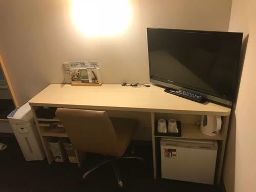 スーパーホテル飛騨・高山のシングルルームの長机、椅子、テレビ、冷蔵庫、電気ポット