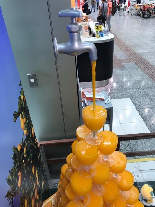 松山空港1階にあるみかんジュースタワーに水道蛇口からみかんジュースが注がれている様子