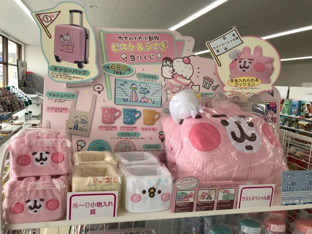セブンイレブンの「カナヘイの小動物当りくじ」の陳列棚に並ぶ当りくじの景品(1等のキャリーバッグの写真など)