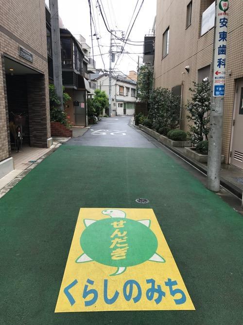 東京都文京区千駄木の「せんだぎ くらしのみち」の亀のイラストが描かれたやや広めの道路