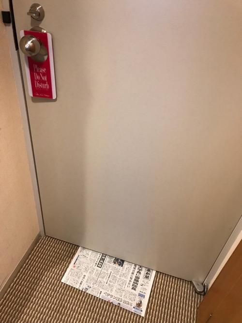 ホテルニューオータニ高岡の客室入口から見た禁煙シングルルーム客室ドア下の隙間から配達された新聞(北日本新聞)