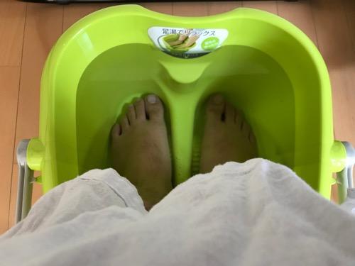イノマタ化学株式会社 リラックス足湯 グリーン 品番-2503(お湯に両足を入れて温めている写真)