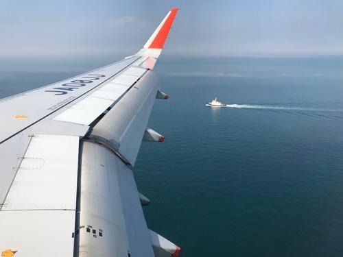 成田空港6時10分発、松山空港7時50分着の飛行機(ジェットスター GK401)の窓から見える海原と船)
