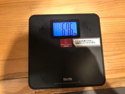 タニタの乗るだけで電源オンする体重計に表示される「67.6kg」という体重 - エクストールイン西条駅前の男湯の脱衣所にて
