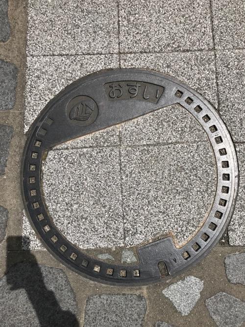 石川県白山市の市章と「おすい」という平仮名が書かれたマンホールの蓋(歩道の石畳で一部が覆われている)