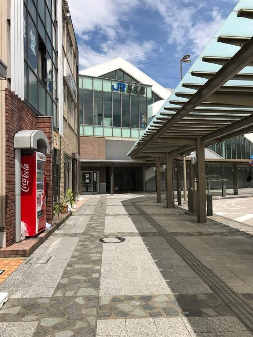 石川県白山市の歩道の石畳で一部が覆われたマンホールの蓋とJR松任駅