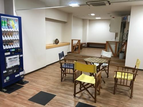 金沢シティホテルのコインランドリーの隣にある自動販売機とテーブルと椅子