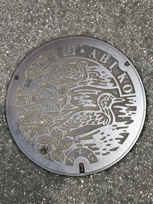 千葉県我孫子市の「MY CITY ABIKO おすい」と書かれ、我孫子市の花・ツツジと市の鳥・オオバンが描かれたマンホールの蓋