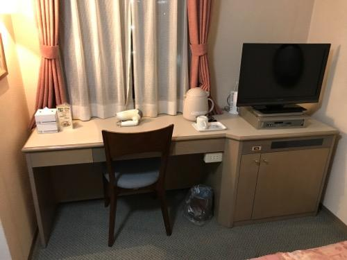 ホテルエコノ金沢駅前のシングルルームの机、椅子、テレビ