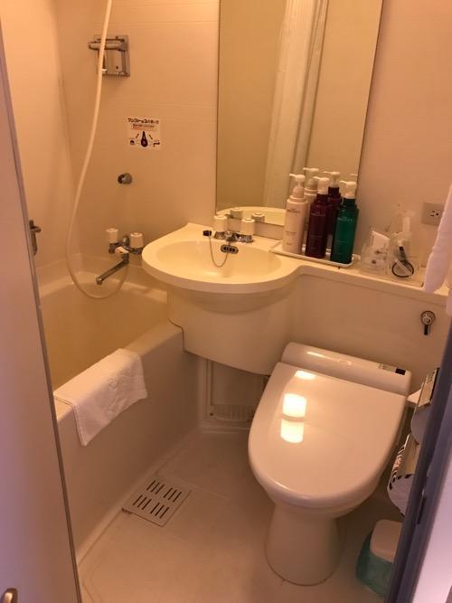 アパホテル金沢駅前のシングルルームの風呂とトイレと洗面台