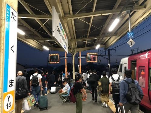 JR詫間駅の柱の駅名標と改札口に向かう乗客達