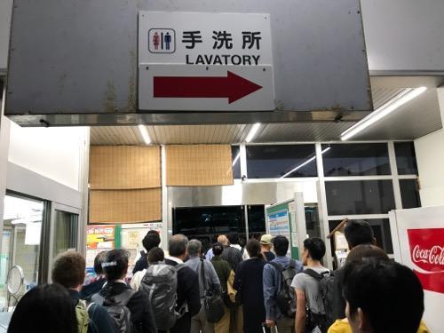 JR詫間駅の改札口前で代替バスに乗るために列をなす乗客達