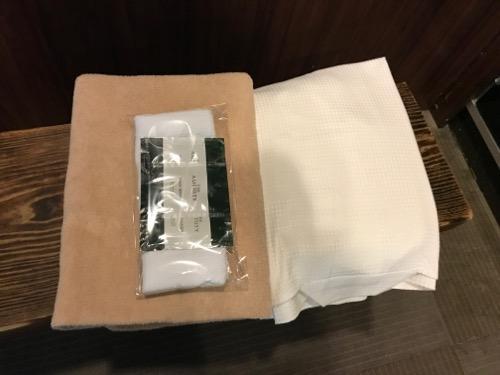 炭の湯ホテル宿泊者に与えられるバスタオル・浴衣・アメニティ(白いハンドタオル・シャンプー、リンス、ボディソープ)