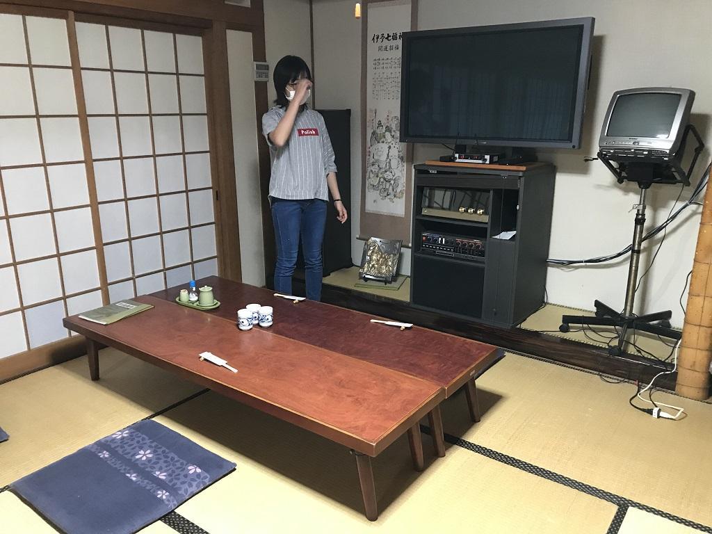 竹山荘の部屋No.11のカラオケ機器側のテーブル前に立つ娘