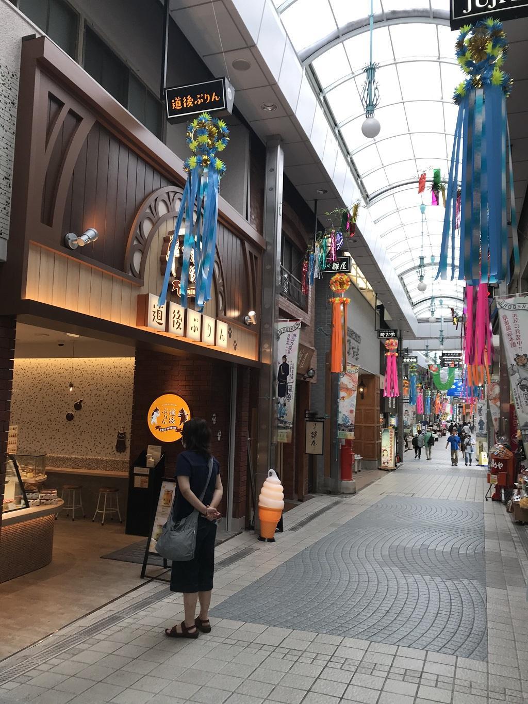 道後商店街の「道後ぷりん」を眺める妻