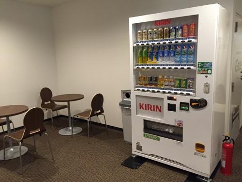 カプセルホテルCUBE広島の自動販売機、共用スペースのテーブルと椅子