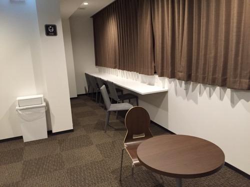 カプセルホテルCUBE広島の窓際の共用スペースの机と椅子