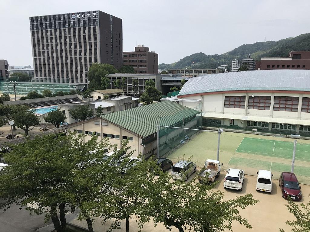 愛媛県立松山北高校の写真(2020年8月:校舎上階から見える風景-テニスコート、体育館、武道場、プール、松山大学)