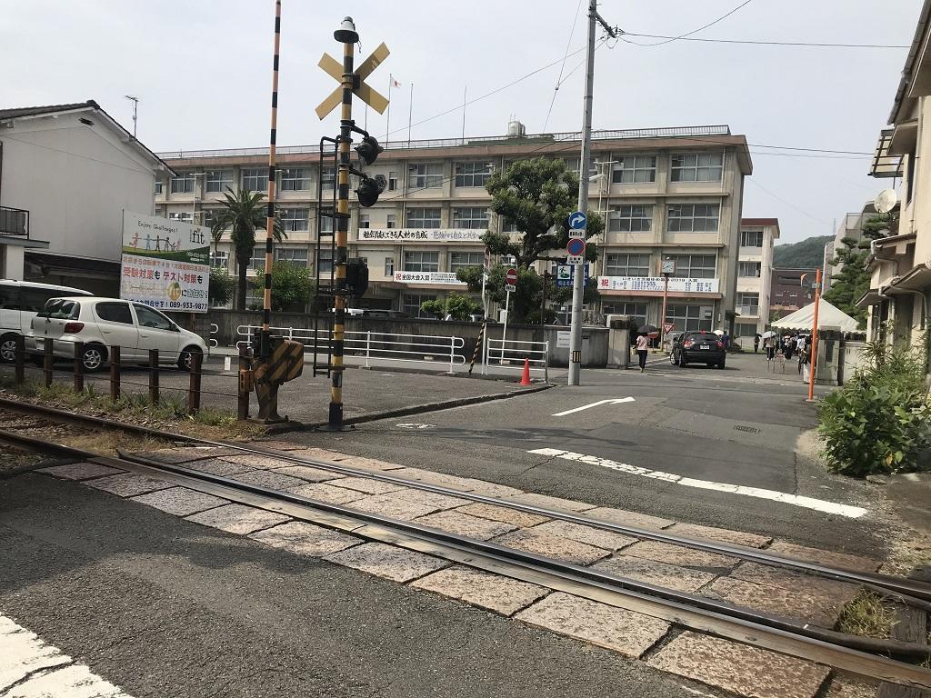愛媛県立松山北高校の写真(2020年8月:伊予鉄道市内電車の踏切の向こう側に見える正門と校舎)